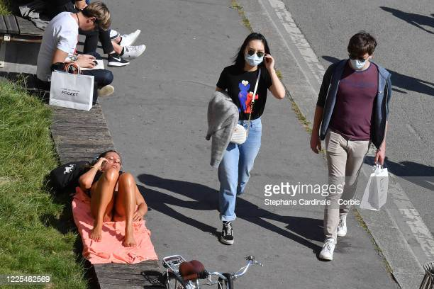 People wearing protective face masks past next a woman who takes sunbathing on the banks of the Seine River after France eased lockdown measures...