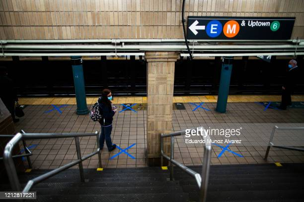 People wearing protective face masks practice social distancing as they wait on marked spots at a subway station during the COVID19 pandemic on May...