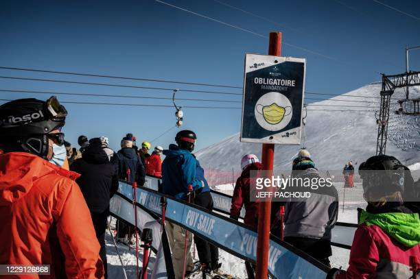People wearing protective face masks queue up to use ski lifts, on the opening day of the Les 2 Alpes French resort on October 17, 2020.
