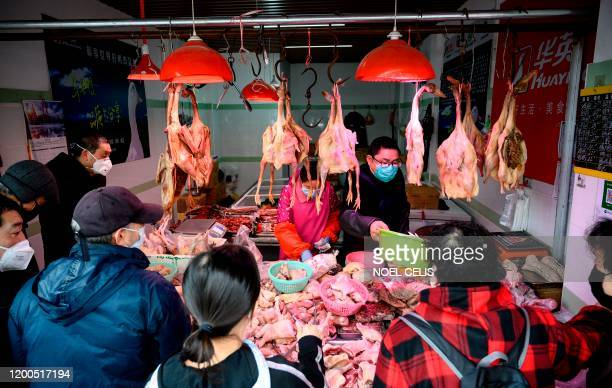 People wearing protective face masks shop at a chicken stall at a wet market in Shanghai on February 13, 2020. - China's official death toll and...