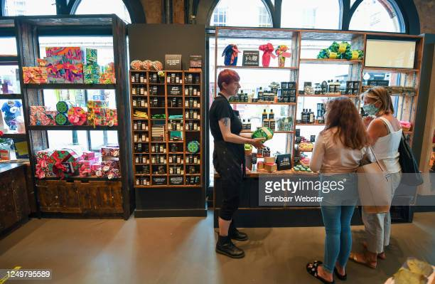 People wearing protective face masks shop in Lush in the town centre on June 15, 2020 in Bournemouth, United Kingdom. The British government have...
