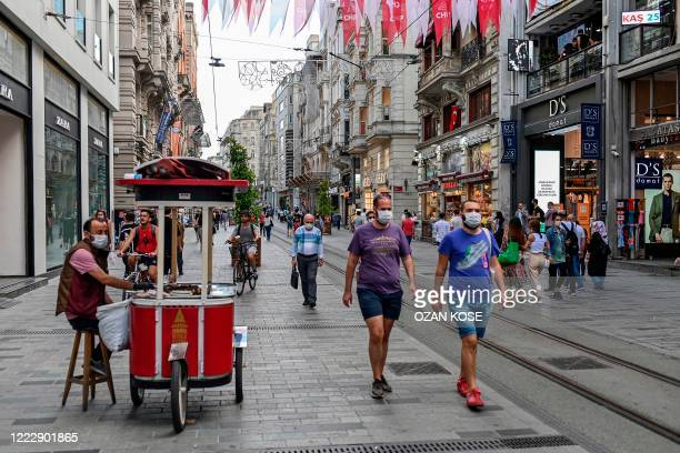 People wearing protective face masks to curb the spread of the novel coronavirus walk in popular shopping avenue Istiklal in Istanbul on June 25 2020...