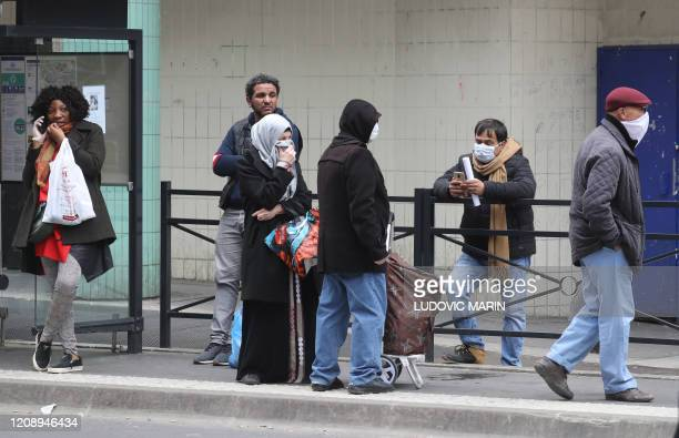 People wearing protective face masks wait at a bus stop on April 2, 2020 in Saint-Denis, near Paris, on the seventeen day of a lockdown aimed at...