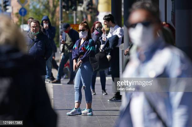 People wearing protective face masks wait for a street tram on the first day face masks became compulsory on public transport in the state of Saxony...