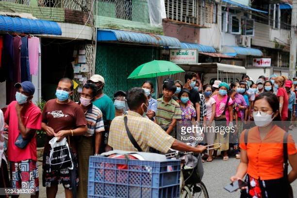 People wearing protective face masks wait in a queue to buy foodstuffs during the coronavirus disease outbreak in Yangon, Myanmar on August 1, 2021....