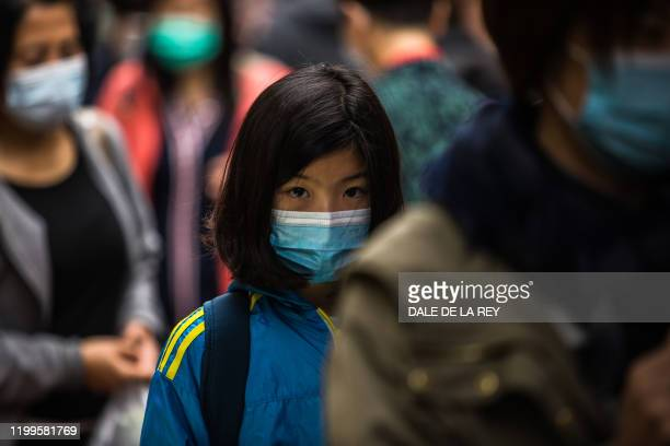 People wearing protective face masks walk along a street in Hong Kong on February 9 as a preventative measure after a coronavirus outbreak which...
