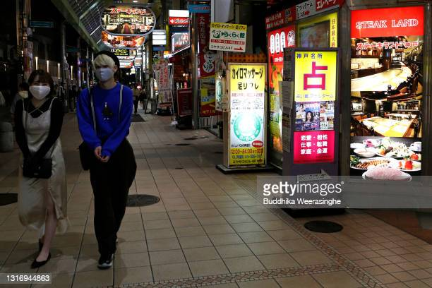 People wearing protective face masks walk along at entertainment street, after adhering to a government request to cease business at 8pm on May 08,...