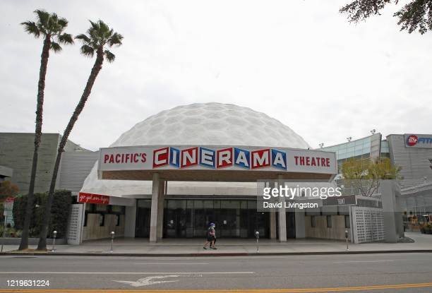 People wearing protective face masks walk by the closed Cinerama Dome theatre during the coronavirus pandemic on April 18, 2020 in Los Angeles,...