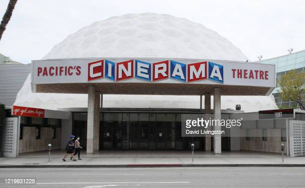 People wearing protective face masks walk by the closed Cinerama Dome theatre during the coronavirus pandemic on April 18 2020 in Los Angeles...