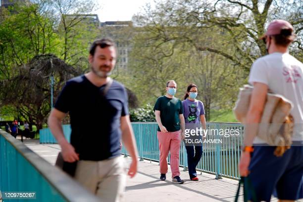 People wearing protective face masks walk in St James's Park in London on April 12 during the nationwide lockdown to combat the novel coronavirus...