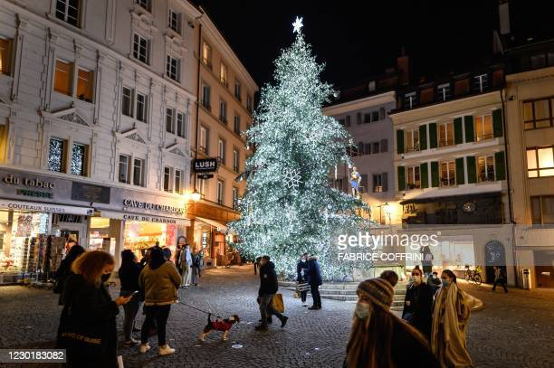 People wearing protective face masks walk past a Christmas tree in the centre of Lausanne on December 17, 2020. - Switzerland, which is failing to...