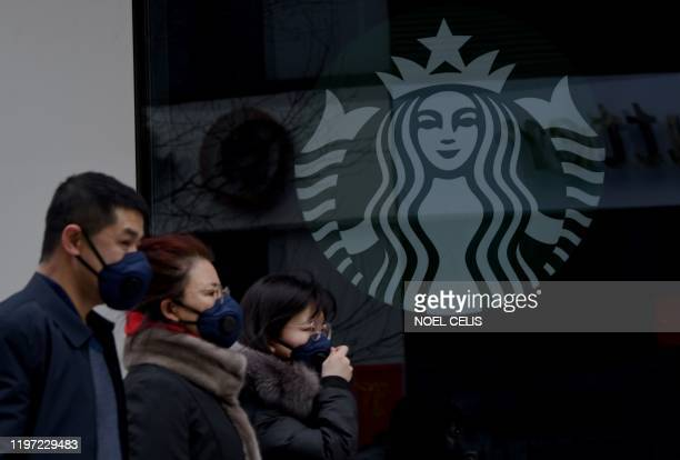 People wearing protective face masks walk past a closed Starbucks coffee shop at a grocery in Beijing on January 29 2020 People in Beijing and across...