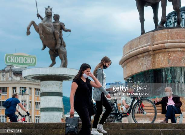 People wearing protective face masks walk past a statue in central Skopje on June 3, 2020 after the country eased lockdown measures taken to curb the...