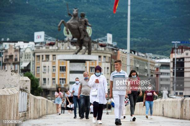 People wearing protective face masks walk past a statue in central Skopje on June 17, 2020. - North Macedonia's main political parties agreed on June...