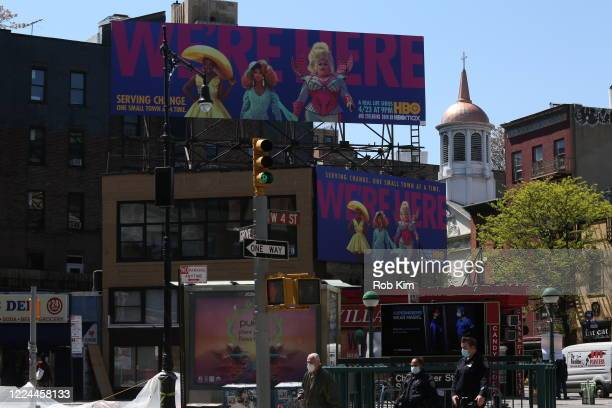 People wearing protective face masks walk past billboards for HBO's We're Here on May 12 2020 in New York City COVID19 has spread to most countries...