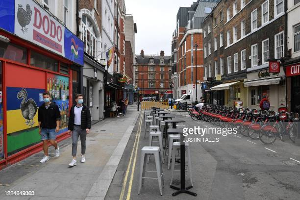 People wearing protective face masks walk past chairs and tables laid out for customers inside a newly created pedestrianised street in Soho in...