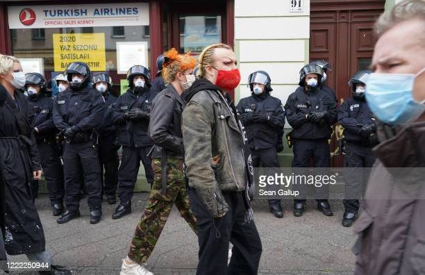 People wearing protective face masks walk past riot police during scattered leftwing protests in Kreuzberg district on May Day during the novel...