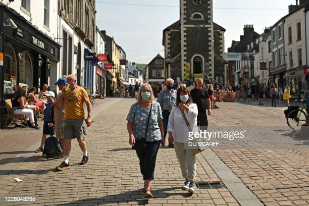 People wearing protective face masks walk through the streets in Keswick in the Lake District in north west England on August 14 as many people take...