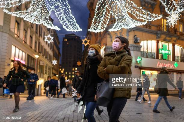 People wearing protective face masks walk under Christmas lights in the centre of Lausanne on December 17, 2020. - Switzerland, which is failing to...