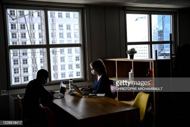 People wearing protective facemasks and respecting social distancing measures, work in a co-working office at the business district of La Defense...