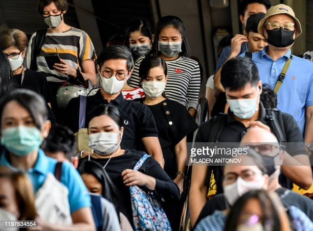 People wearing protective facemasks leave the city commuter train station in Bangkok on January 31 2020 The World Health Organization declared a...