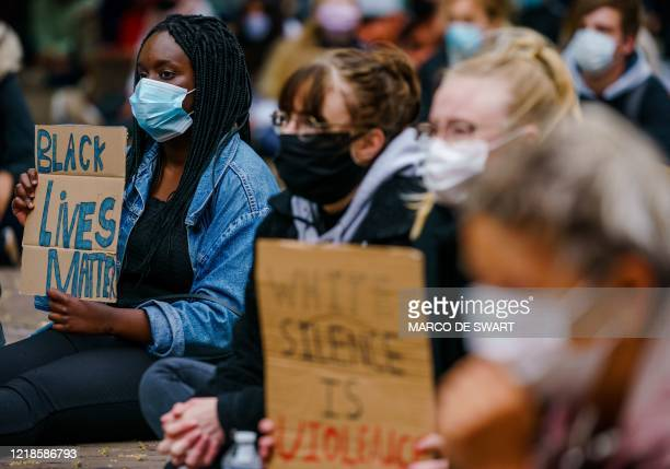 People wearing protective facemasks sit and hold placard as they demonstrate at Abdijplein in Middelburg, on June 8 during a 'Black Lives Matter'...