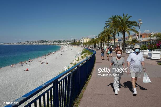 """People wearing protective fave masks walk along the """"Promenade des anglais"""" on the French Riviera city of Nice, southern France, on May 30 as France..."""