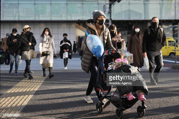 People wearing protective mask walk on the street on January 13 in Tokyo, Japan. Japan's Prime Minister Yoshihide Suga is set to expand to the State...