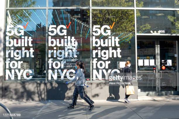 People wearing protective masks and gloves pass by a Verizon store advertising 5G in New York amid the coronavirus pandemic on April 28 2020 in New...