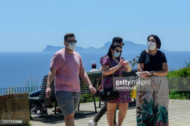 People wearing protective masks are next to the sea in front of Capri Island Italian government has stopped a nationwide lockdown that was due to the...