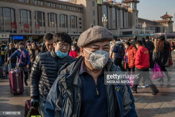 People wearing protective masks arrive at Beijing railway station to head home for the Lunar New Year on January 21, 2020. - China has confirmed...