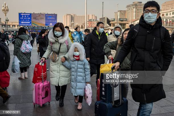 TOPSHOT People wearing protective masks arrive at Beijing railway station to head home for the Lunar New Year on January 21 2020 China has confirmed...