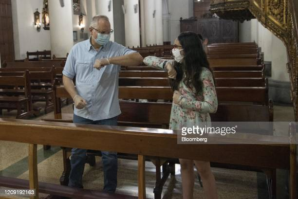 People wearing protective masks bump elbows during a Palm Sunday mass in Caracas Venezuela on Sunday April 5 2020 Amid the coronavirus as the world's...