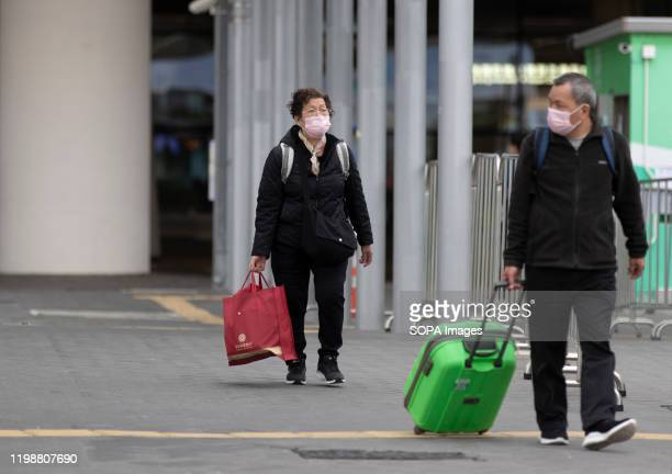 People wearing protective masks carrying luggage outside the arrival hall of the Hong Kong port Chief Executive Carrie Lam said on Monday that all...