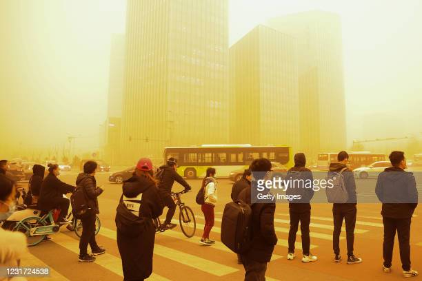 People wearing protective masks cross a street during a sandstorm on March 15, 2021 in Beijing, China. The Chinese capital and the northern parts of...