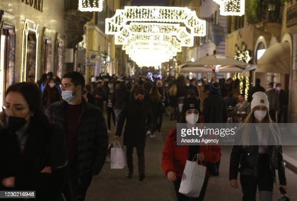 People wearing protective masks crowd Via Condotti, lightened by Christmas lights, in downtown Rome, Italy, on December 19, 2020. Italian government...