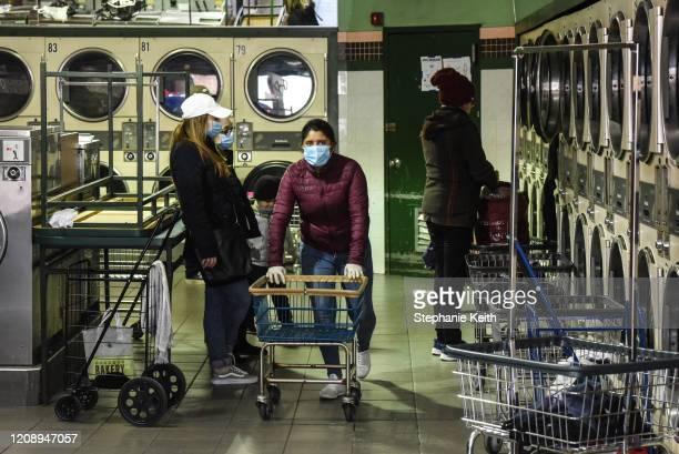 People wearing protective masks do their laundry in a laundromat near Myrtle Ave in the Bushwick neighborhood of Brooklyn on April 2 2020 in New York...