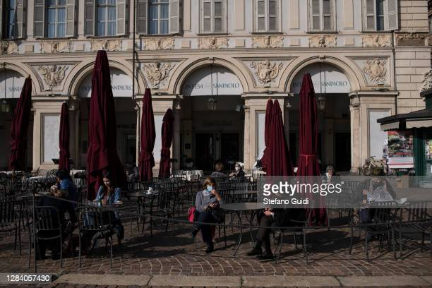 People wearing protective masks drink coffee at Piazza San Carlo during the last day before new lockdown measures for the Piedmont Region on November...