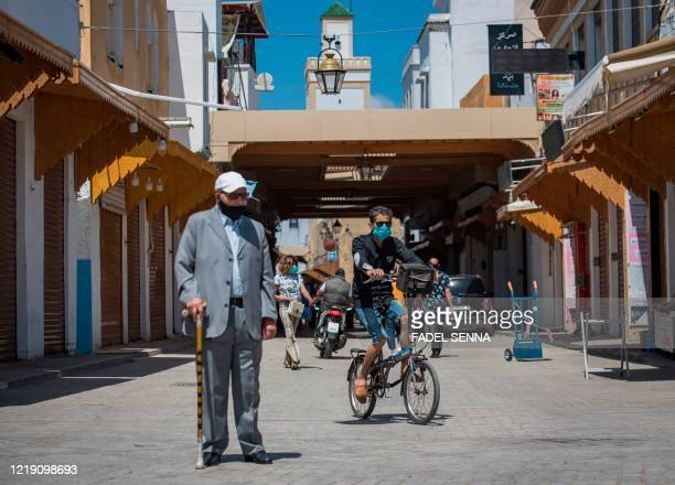 People, wearing protective masks due to the COVID-19 pandemic, pass by closed shops in the Moroccan capital Rabat on June 10 as the government...
