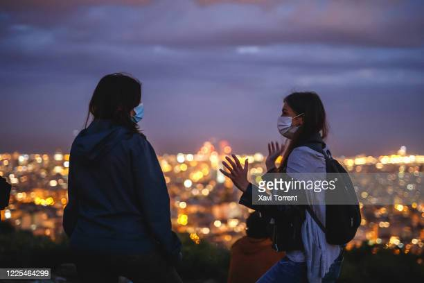 People wearing protective masks enjoy the sunset at the Carmel hill on May 17, 2020 in Barcelona, Spain. Some parts of Spain have entered the...