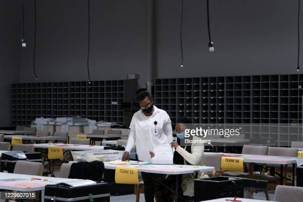 People wearing protective masks hand count 2020 Presidential election ballots during an audit at the Gwinnett County Voter Registration office in...