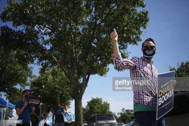 People wearing protective masks hold signs in support of Charles Booker a Democratic US Senate candidate outside a polling location in Louisville...