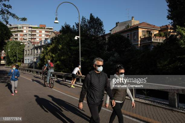 People wearing protective masks jog and run along the Naviglio Martesana canal on May 04 2020 in Milan Italy Starting today more than 4 millions of...