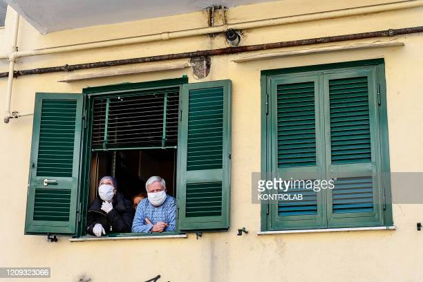 People wearing protective masks look out of a window at home, in Fuorigrotta district for the pandemic of Coronavirus Covid-19 to end. Italy has now...