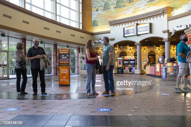 People wearing protective masks maintain social distancing as they wait in line for a concessions counter at a Regal Cinemas theater in Austin,...