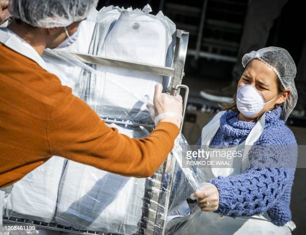 People wearing protective masks move packages distributed during the start of the meal delivery campaign of the platform justpeople.nl in...