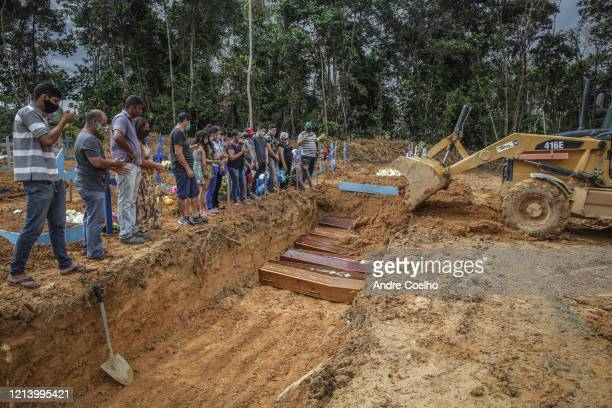 People wearing protective masks observe to the graves with the remains of their relatives during a mass burial of coronavirus pandemic victims at the...