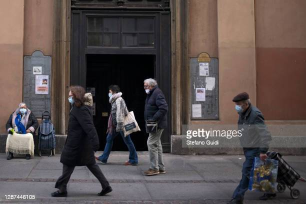 People wearing protective masks pass a church on Via Milano on November 24 2020 in Turin Italy While the whole country is in various degress of...