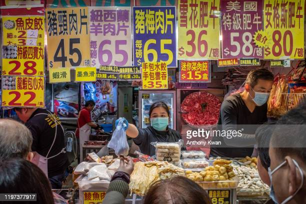 People wearing protective masks purchase meat products at a market on January 29, 2020 in Hong Kong, China. Hong Kong government will deny entry for...