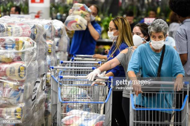 People wearing protective masks queue for food packages at a local market on March 31, 2020 in Belo Horizonte, Brazil. Belo Horizonte city council...